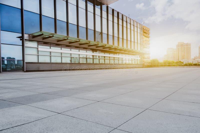 Leerer Ziegelsteinboden mit modernem Gebäude im Hintergrund stockfotos