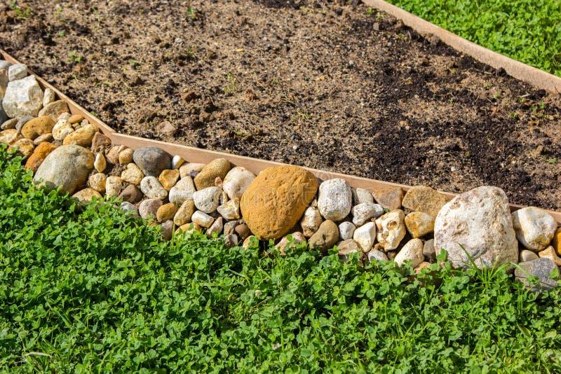 Leeres Blumenbeet gestützt mit Steinen stockbild