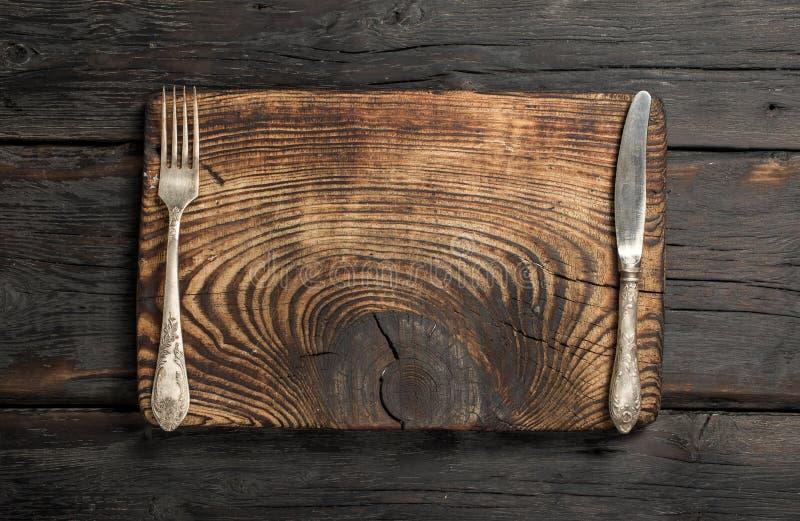 Leeres Brett der Weinlese mit Gabel und Messer stockbilder
