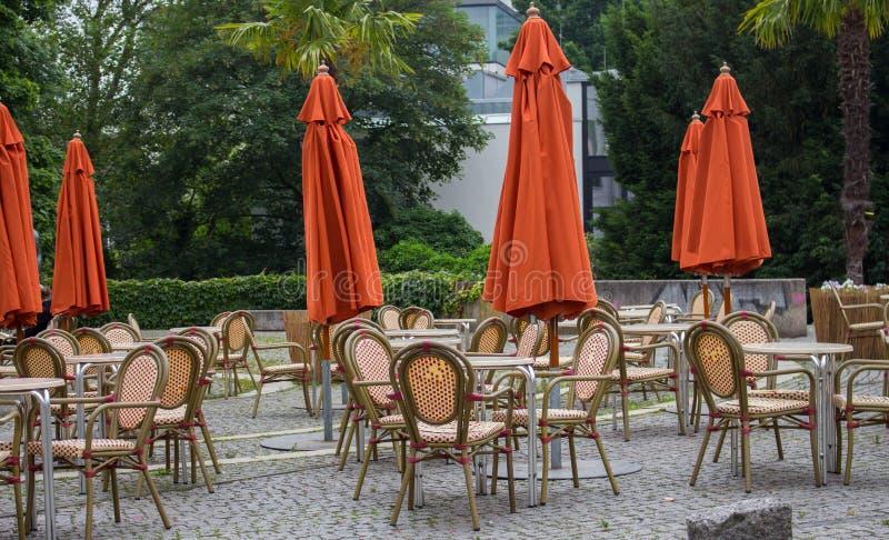 Leeres Café im Freien mit geschlossenen Regenschirmen Straßencafé mit leeren Tabellen und Stühlen Restaurantmöbelkonzept stockfotos