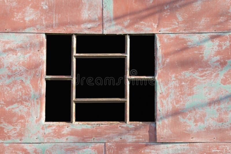 Leeres Fenster mit Gitter auf einem Metallbau malte Rot lizenzfreies stockbild