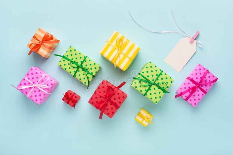 Leeres Geschenktag mit Band u. bunten Geschenkboxen stockbilder