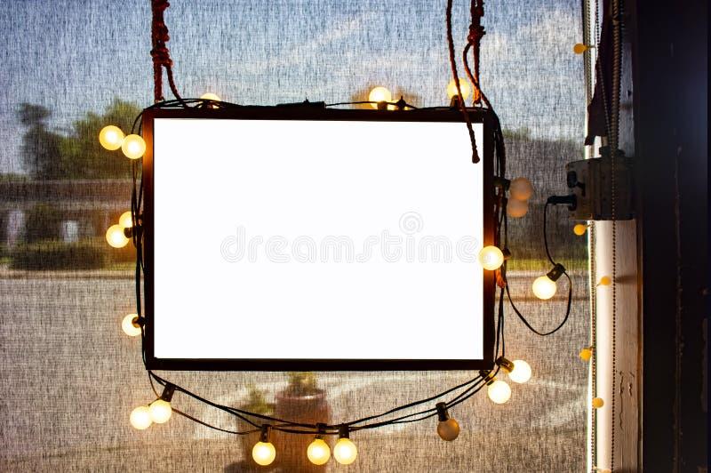 Leeres Hängeschild umgeben durch Parteilichter im Shopfenster mit halb-transparenten dunklen Solarschatten hinten und schwach ges lizenzfreie stockfotografie
