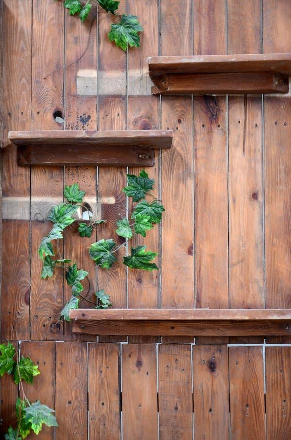 Leeres hölzernes Regal auf hölzerner dekorativer Wand in der dunkelbraunen Farbe stockfoto