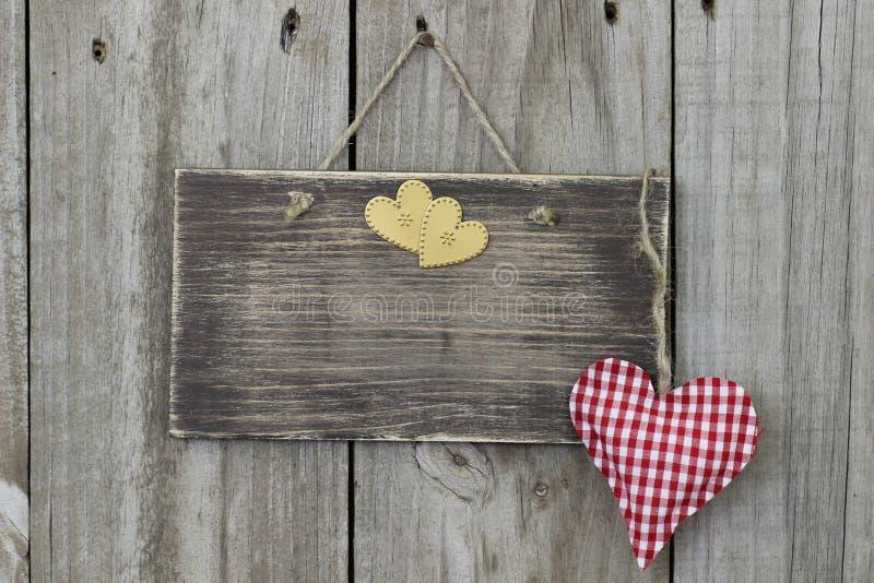Leeres Holzschild, das an der hölzernen Tür mit Gingham- und Goldherzen hängt stockbild