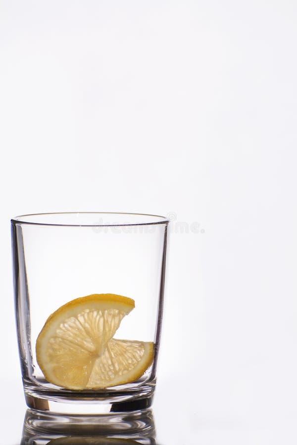 Leeres Kristallglas mit Reflexion auf Weiß lokalisierte Hintergrund mit zwei Stücken der Zitrone lizenzfreie stockbilder