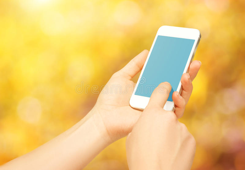 Leeres leeres Telefongerät in den Händen der Frau auf Natur im Herbst lizenzfreies stockfoto