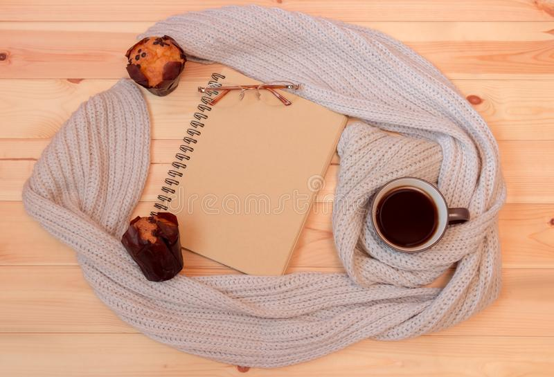 Leeres Notizbuch, Becher heißer Kaffee eingewickelt im Schal, Gläser und Muffins stockfoto