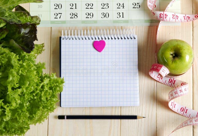 Leeres Notizbuch mit Gemüsesalat und Apfel lizenzfreie stockfotos