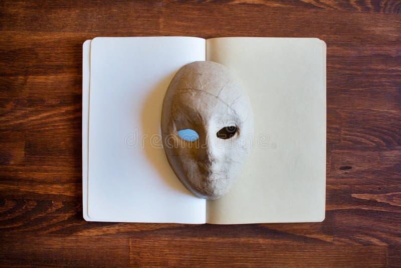 Leeres Notizbuch mit papier-mâché Maske stockfotos