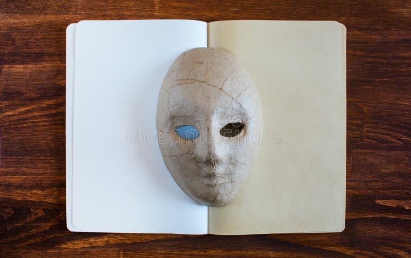 Leeres Notizbuch mit Papiermachemaske lizenzfreies stockfoto