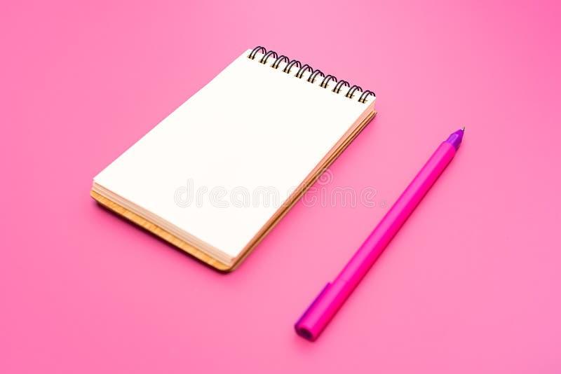 Leeres Notizbuch mit Spirale für die Anwendung von Aufklebern und von Stift auf rosa Hintergrund lizenzfreie stockfotos
