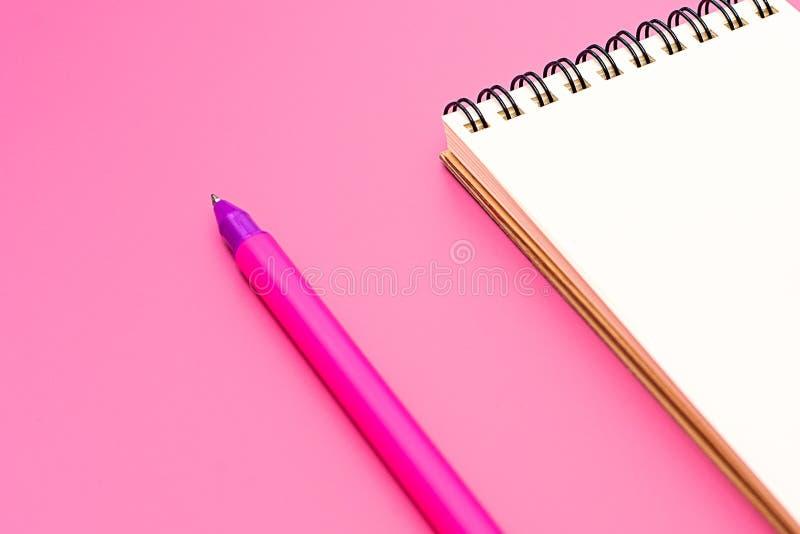Leeres Notizbuch mit Spirale für die Anwendung von Aufklebern und von Stift auf rosa Hintergrund lizenzfreies stockfoto