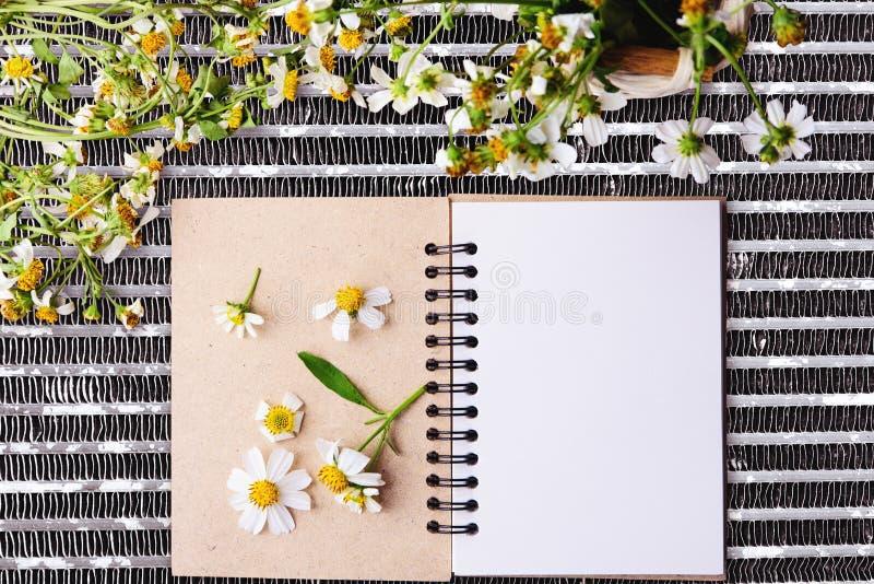 Leeres Notizbuch mit weiße Blume und bas ket der Blume auf Stahlnettotabelle lizenzfreies stockfoto