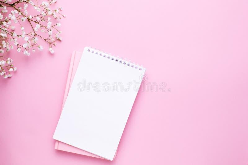 Leeres Notizbuch und wei?e Blumen auf rosa Pastelltischplatteansicht in flache gelegte Art Frauenarbeitsschreibtisch stockbild