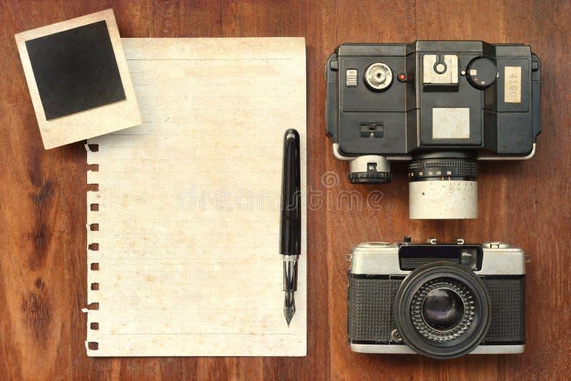 Leeres Papier mit Stift, Fotorahmen und Kamera auf hölzernem Hintergrund lizenzfreie stockbilder
