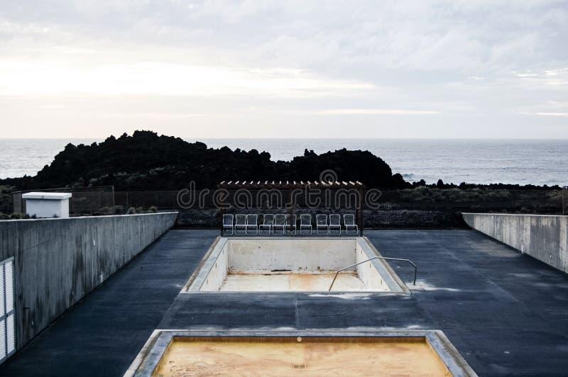 Leeres Pool mit Stühlen nahe der Klippe und einem Meer lizenzfreies stockfoto