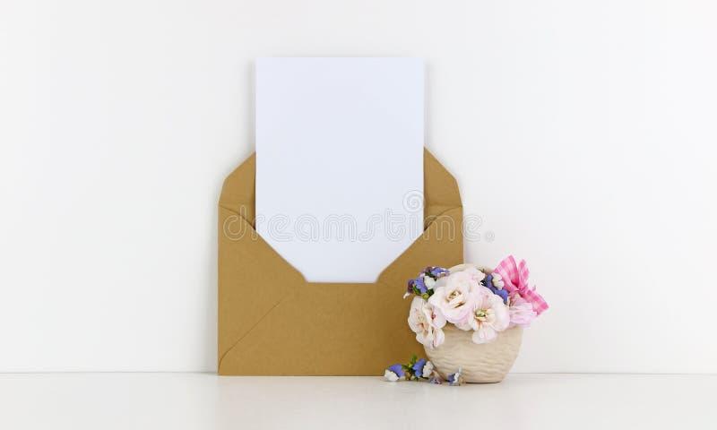 Leeres Postkartenmodell mit Kraftpapierumschlag und weißen Blumen lizenzfreie stockbilder