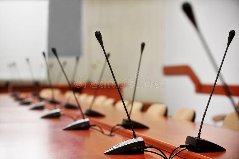 Leeres Pressekonferenz romm mit Mikrophonen lizenzfreie stockfotografie