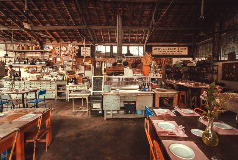 Leeres Restaurant im rustikalen Gebäude, in der offenen Küche und in der Bar mit biologischem Lebensmittel, Getränken und Weinles stockbild
