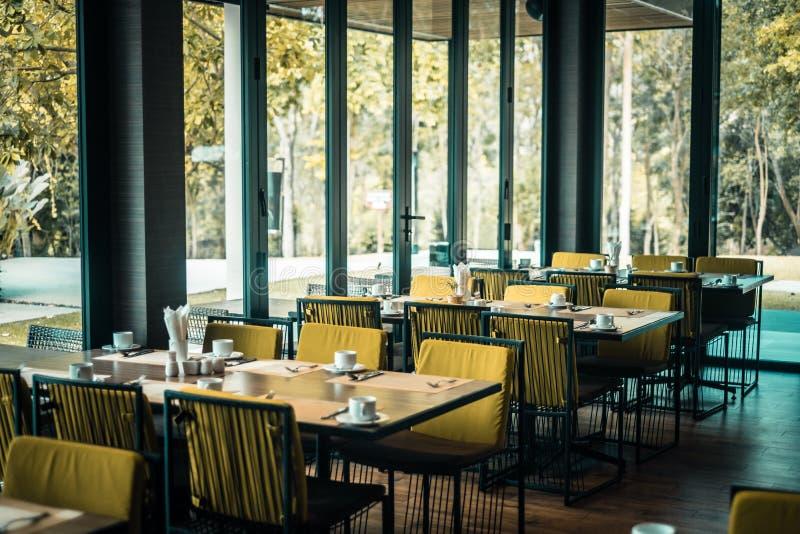 Leeres Restaurantteil des Hotels mit Tabelle und Lehnsessel nahe Fenstern und Gartenansicht lizenzfreies stockbild