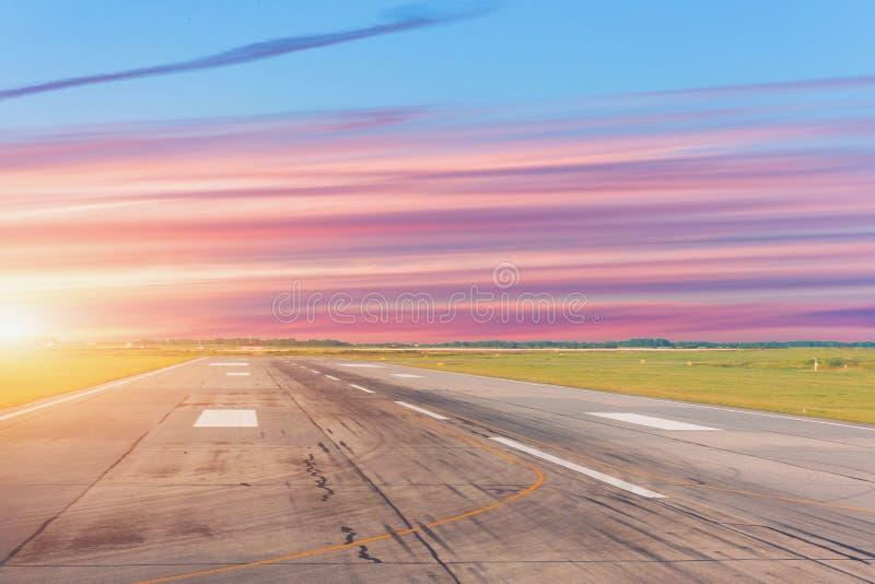 Leeres Rollbahnflughafenflugfeld und -wolken bei Sonnenuntergang stockfotos