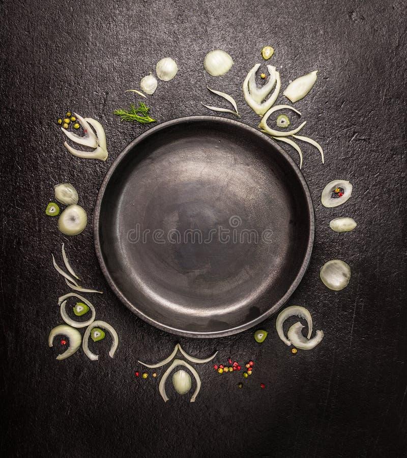 Leeres Schwarzblech mit Rahmen von Zwiebelscheiben und -gewürzen auf dunklem Steinhintergrund, Draufsicht stockbilder