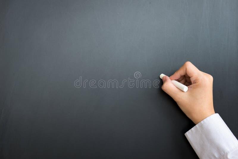 Leeres schwarzes Brett mit der Hand und Kreide stockbild