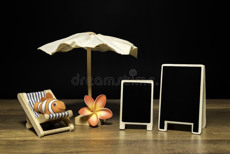 Leeres schwarzes Brett mit Strandschirm und Bett mit Clownfischen und -blume stockbild