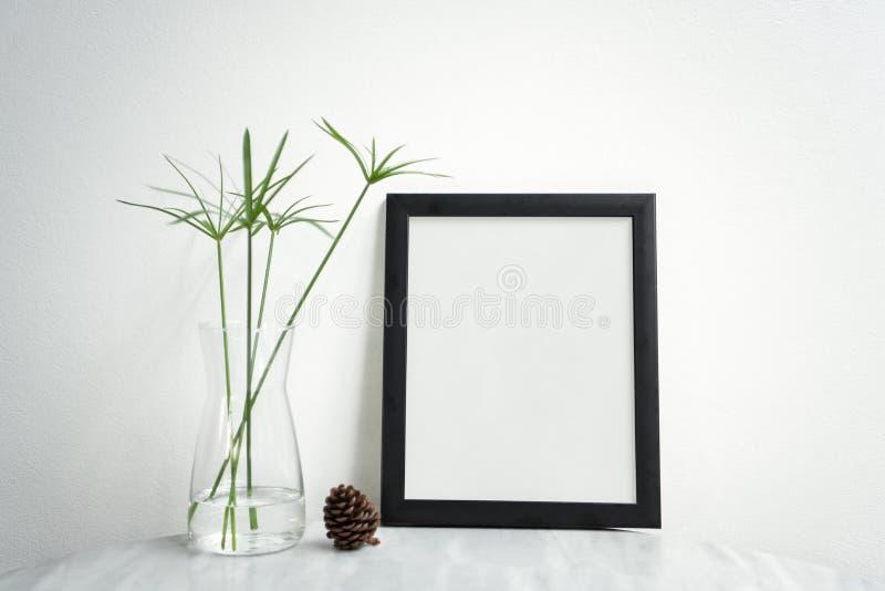 Leeres schwarzes Fotofeld und -Vase auf Tabelle für Design-Modell lizenzfreie stockfotografie