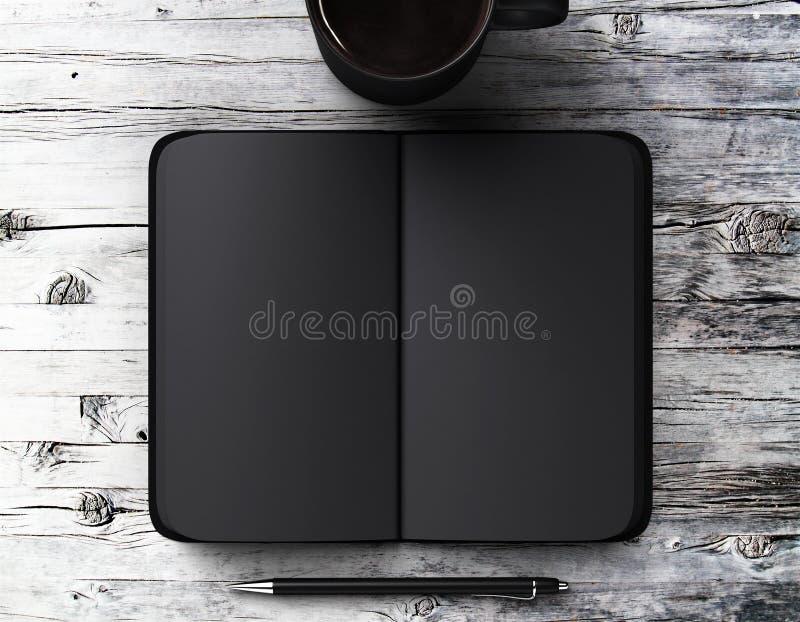 Leeres schwarzes Tagebuch mit Stift und ein Tasse Kaffee auf einem Holztisch lizenzfreie stockfotos