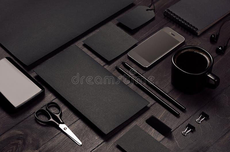 Leeres schwarzes Unternehmensbriefpapier mit Telefon auf dem dunklen stilvollen hölzernen Hintergrund, geneigt, Nahaufnahme stockfotografie