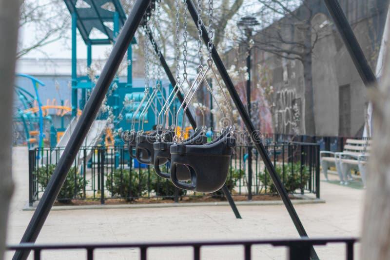 Leeres Schwingen auf einem New- York Cityspielplatz, an einem regnerischen Tag lizenzfreies stockfoto