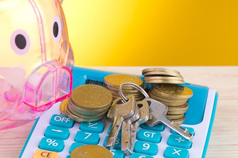 Leeres Sparschwein, Münze mit Schlüsselbund stapelnd auf Taschenrechner lizenzfreie stockfotografie