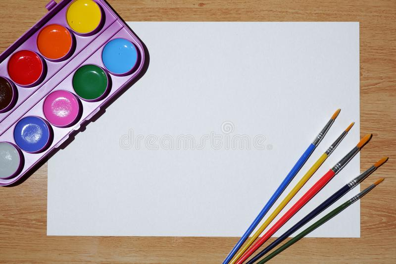 Leeres Weißbuch, Satz Aquarellfarben und Satz Malerpinsel lizenzfreies stockbild