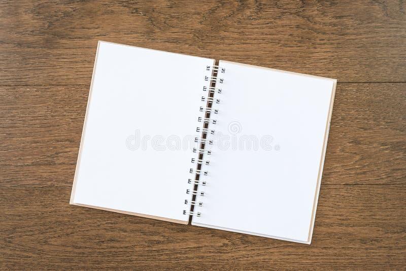 Leeres weißes Notizbuch auf hölzernem Beschaffenheitshintergrund stockfotografie
