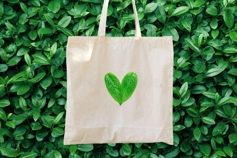 Leeres weißes Modell-Leinenbaumwolle Tote Bag auf grünem Bush-Baum-Laub-Hintergrund Herzlogo von den Blättern Freundliche Art der lizenzfreies stockbild