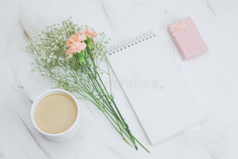 leeres weißes Notizbuch, Kaffeetasse, Geschenkbox und boquet der Gartennelke und der Gypsophilablumen auf einem Marmorhintergrund stockfotografie
