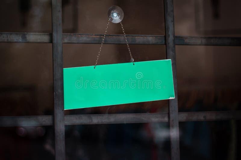 Leeres Zeichen auf Geschäftsfenster - leeres Zeichen, das an der Speichertür hängt stockbilder