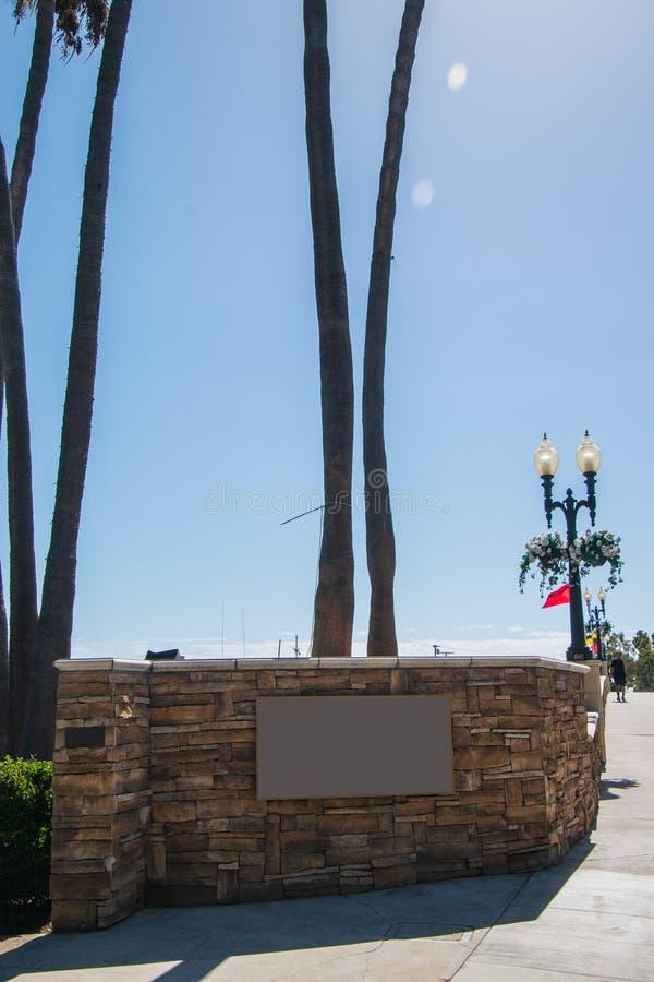 Leeres Zeichen gelegen durch eine Straße auf einer Steinwand mit Palmestämmen im Hintergrund stockfotografie