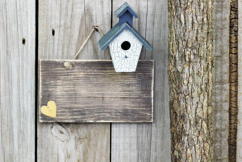 Leeres Zeichen mit blauem und weißem Vogelhaus nahe bei Baum lizenzfreie stockfotografie