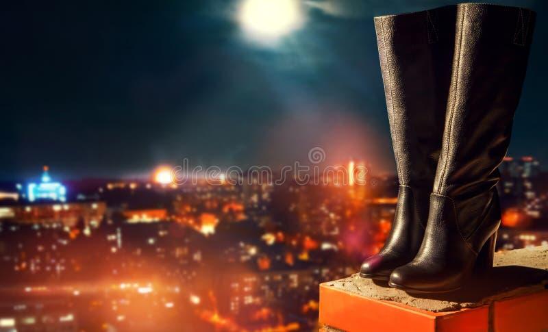 Leerlaarzen die zich op dak bevinden die stad overzien bij nacht stock foto's
