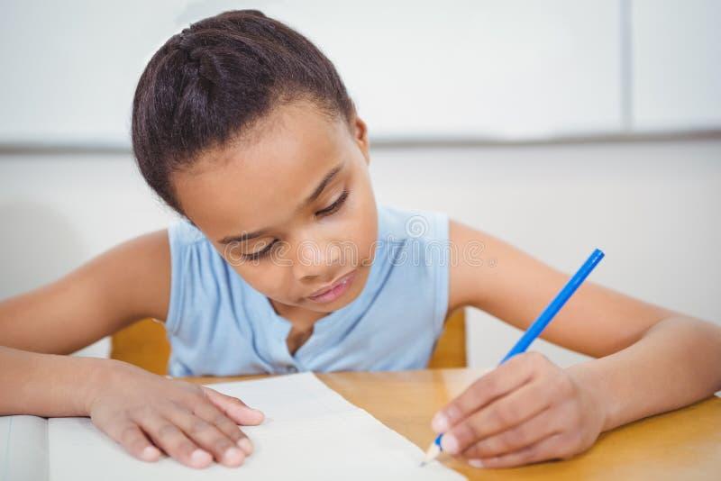 Leerling die in een notitieboekje schrijven stock foto