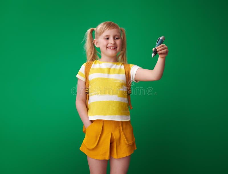 Leerling die met grote pen in lucht tegen groene achtergrond schrijven royalty-vrije stock fotografie