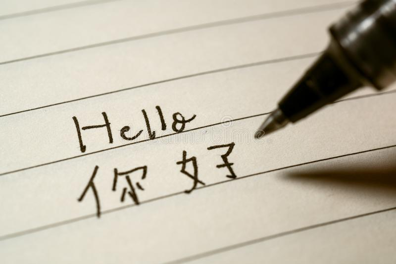 Leerling die van de beginners de Chinese taal Hello-woord Nihao in Chinese karakters op een notitieboekje schrijven stock afbeelding