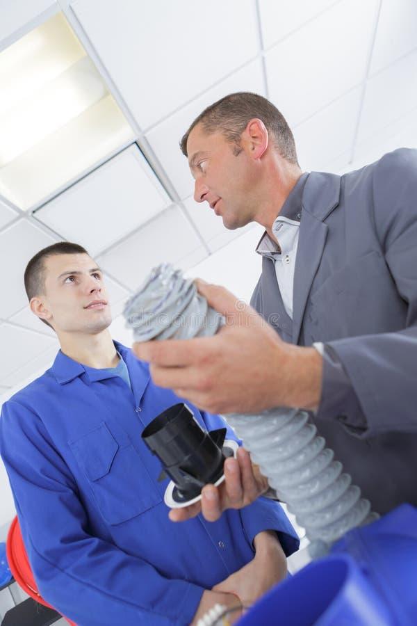 Leerling op het gebied die van airconditioningssystemen met leraar werken stock afbeeldingen