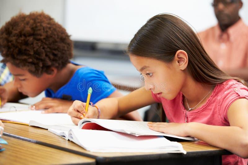 Leerlingen die bij Bureaus in Klaslokaal bestuderen stock fotografie