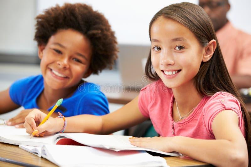 Leerlingen die bij Bureaus in Klaslokaal bestuderen royalty-vrije stock afbeeldingen