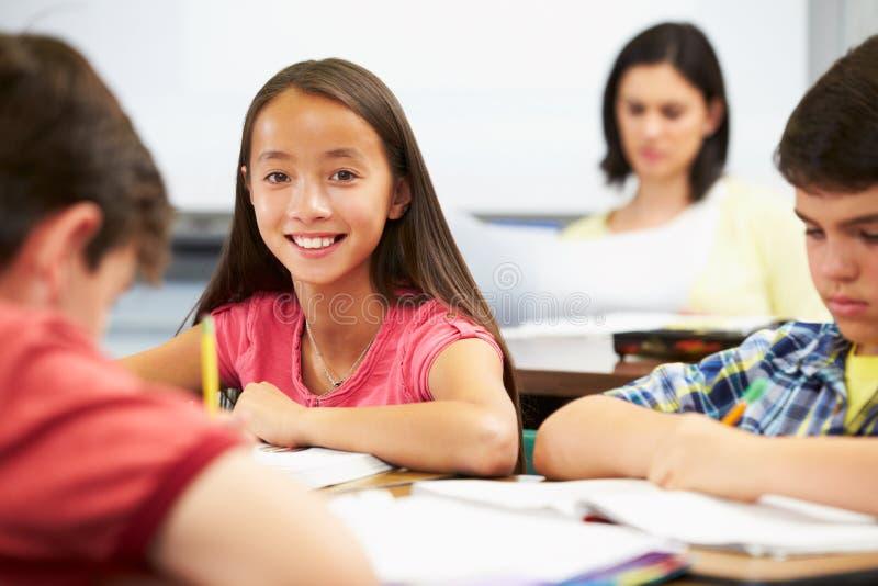 Leerlingen die bij Bureaus in Klaslokaal bestuderen royalty-vrije stock fotografie
