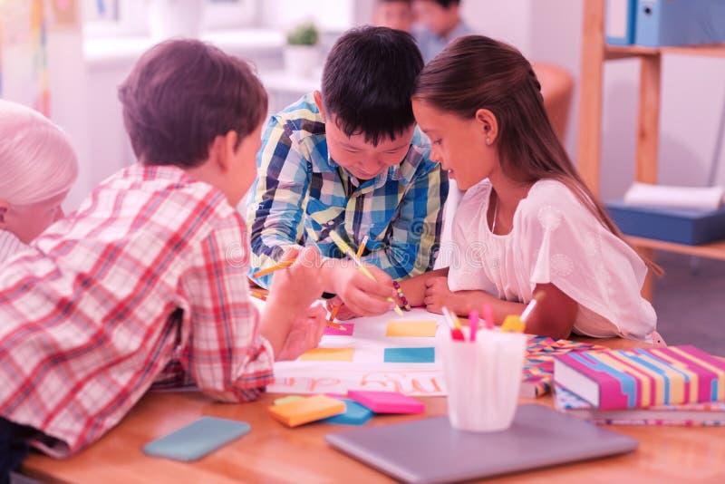 Leerlingen die hun schoolproject in groep maken royalty-vrije stock afbeeldingen